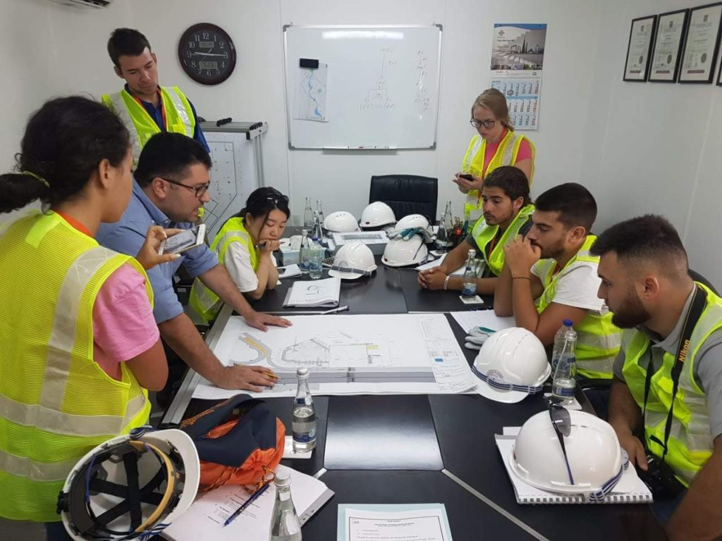 A group of students gather around a set of blueprints, which are spread out on a table. The students are wearing reflective vests, and their hard hats are sitting on the table.