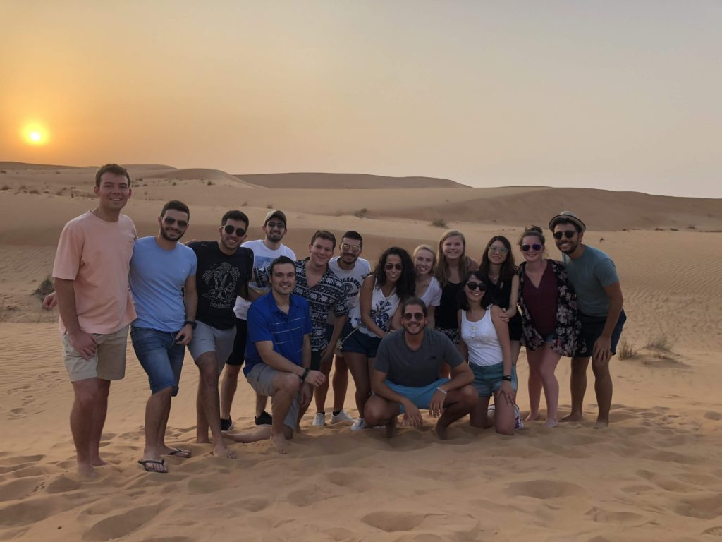 A group of fourteen students pose for a photo on a sand dune at sunset