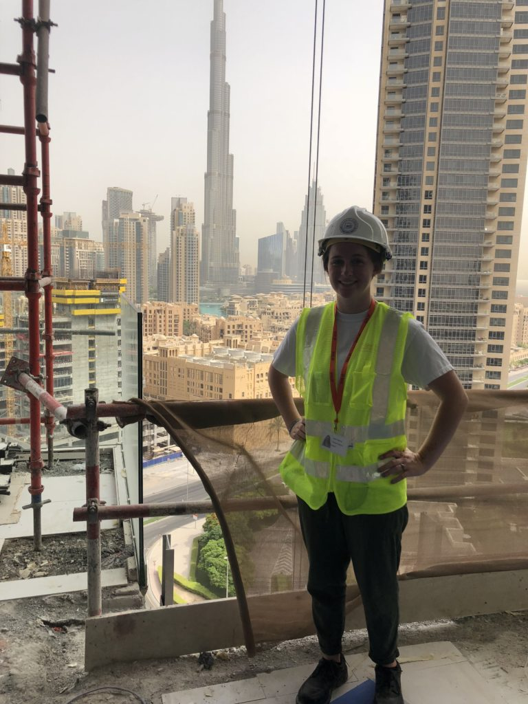 Picture of Haley standing at a construction site, with the city skyline behind her. She wears a reflective vest and hard hat.