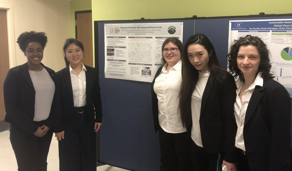 Simone and four other students stand in front of a research poster