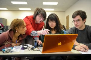 A professor works with a group of undergraduate students.