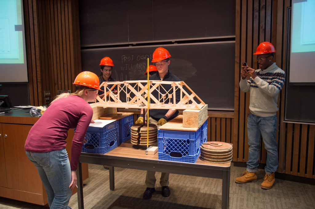 Civil engineering students test the bridge they built as part of the ECS 101 end-of-semester competition.
