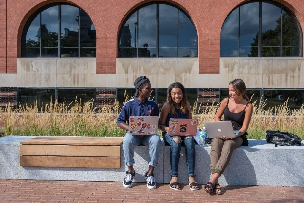 Students collaborate outside of the Schine Student Center.