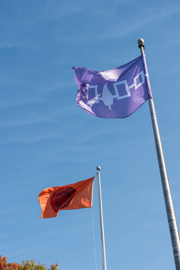 The Haudenosaunee flag flies next to the Syracuse University flag on the Quad.